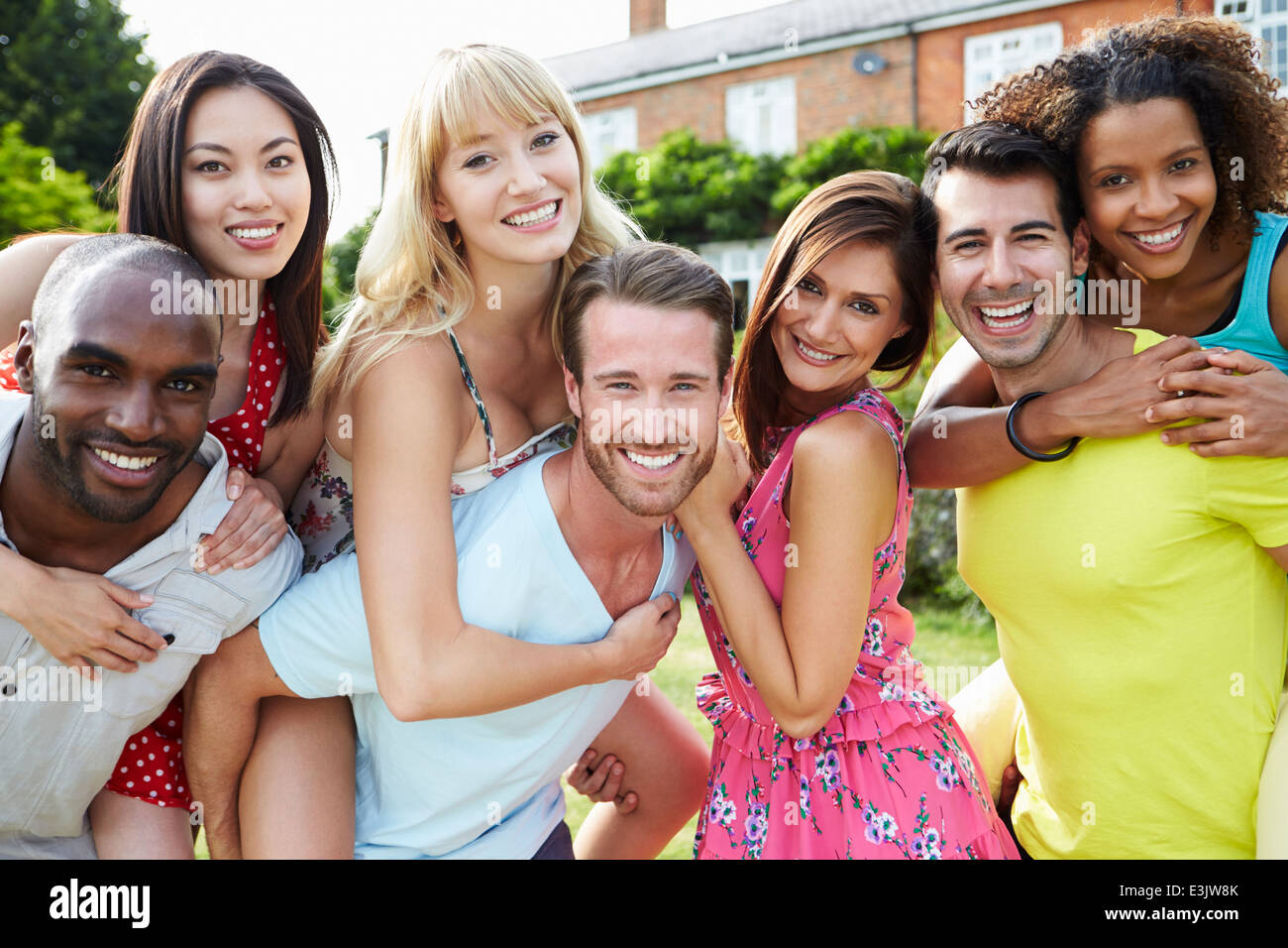 Portrait Of Friends Relaxing In Summer Garden Together - Stock Image