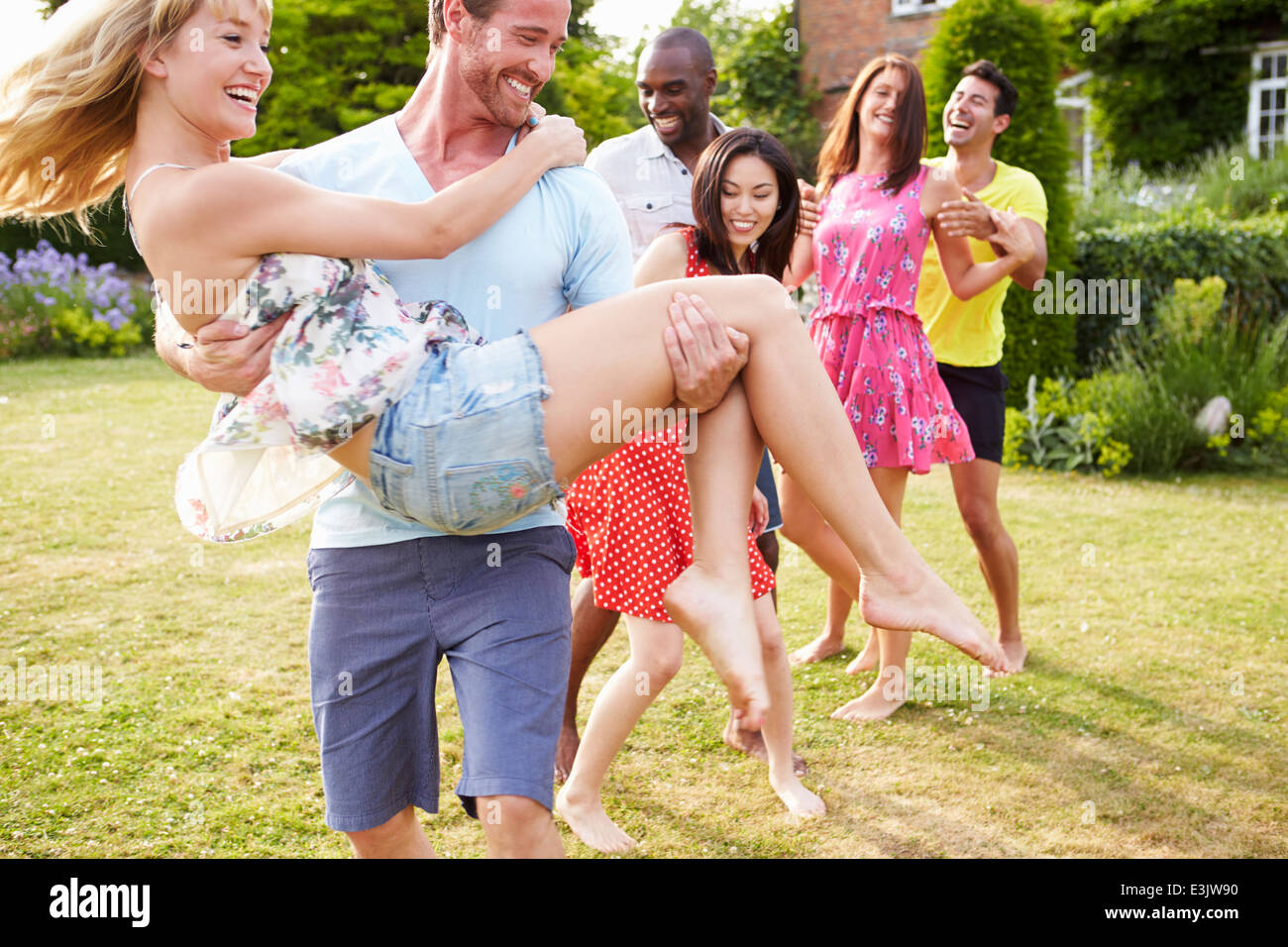 Friends Relaxing In Summer Garden Together - Stock Image