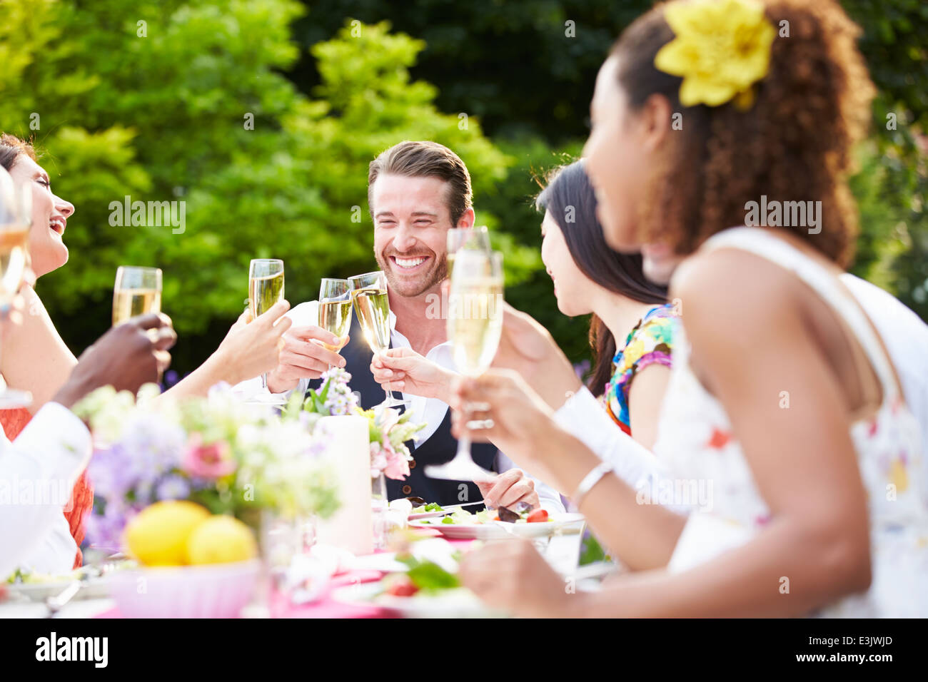 Group Of Friends Enjoying Outdoor Dinner Party - Stock Image