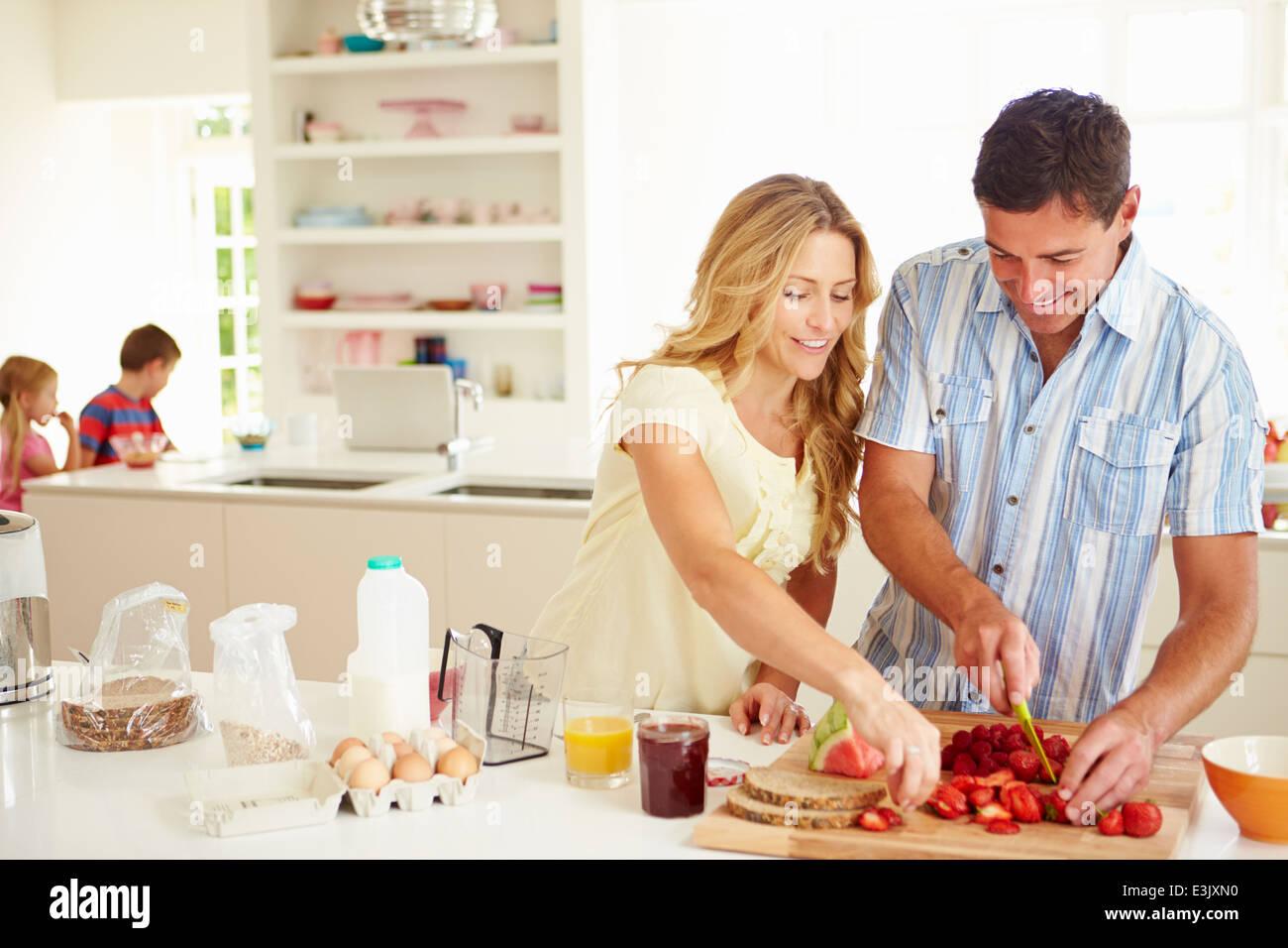 Parents Preparing Family Breakfast In Kitchen - Stock Image
