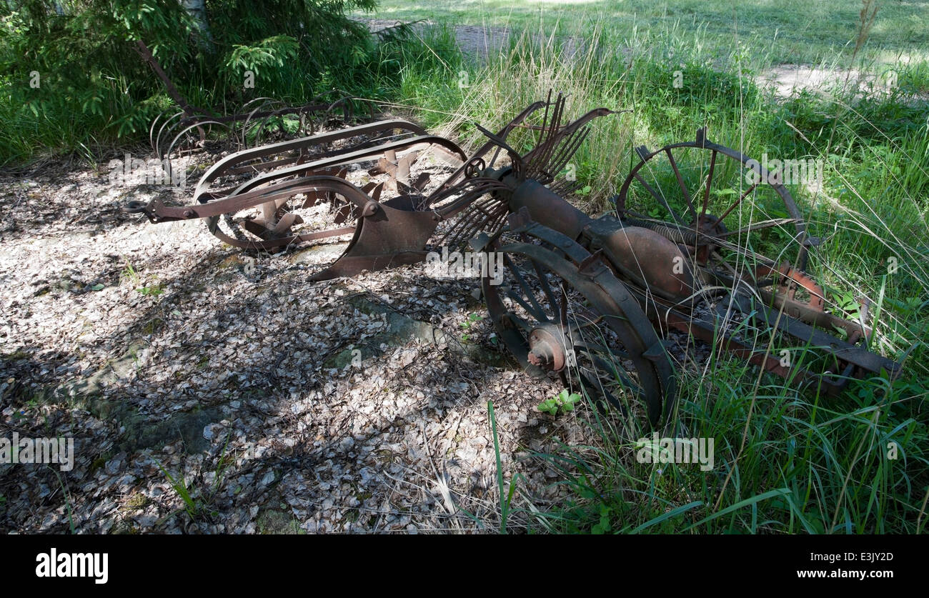 old farm equipment rusting in forest, Finland - Stock Image