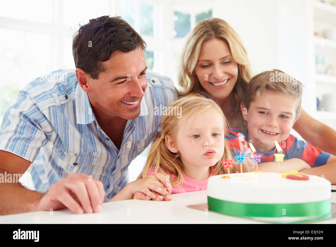 Family Celebrating Daughters Birthday With Cake - Stock Image