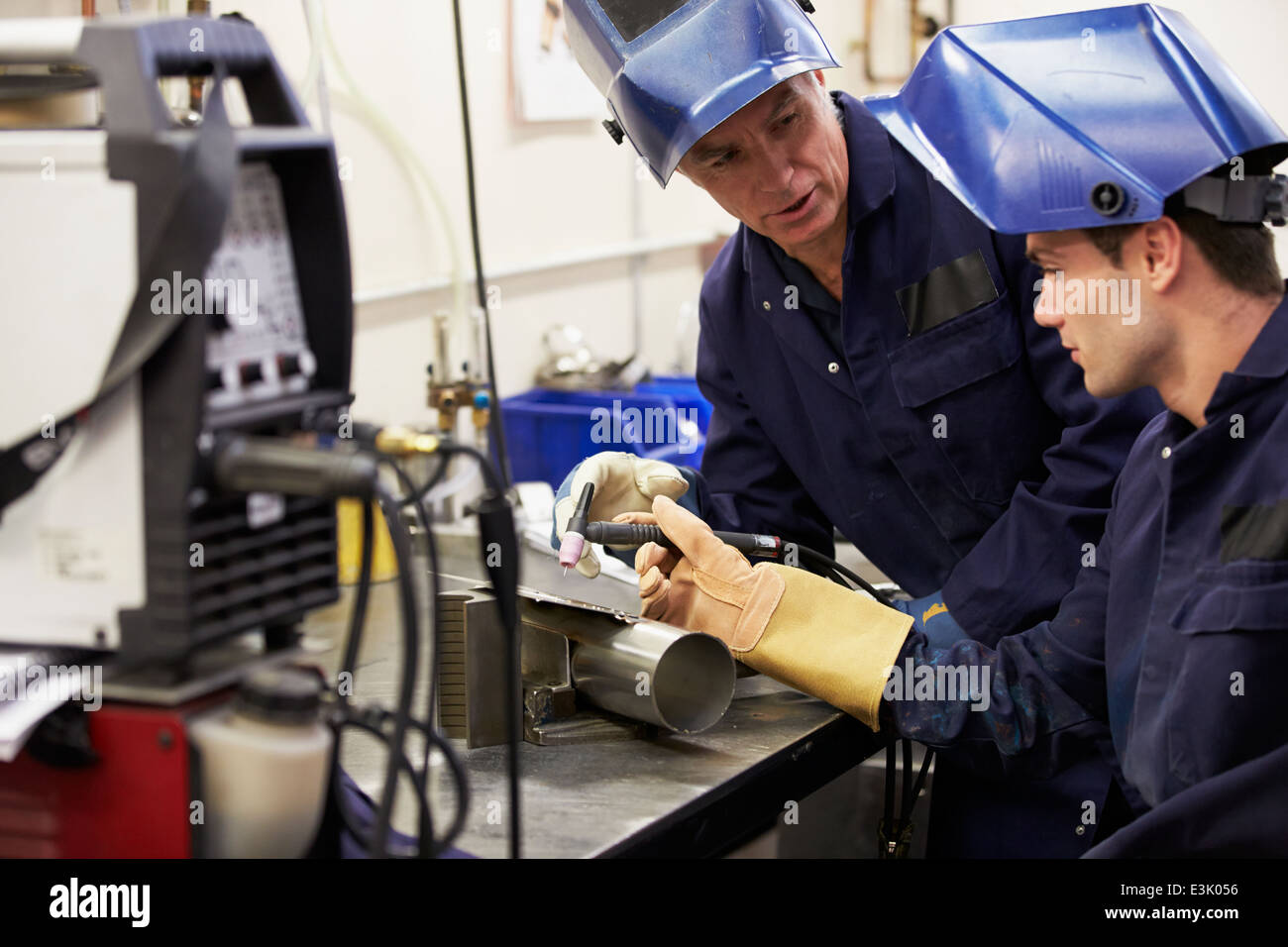 Engineer Teaching Apprentice To Use TIG Welding Machine - Stock Image