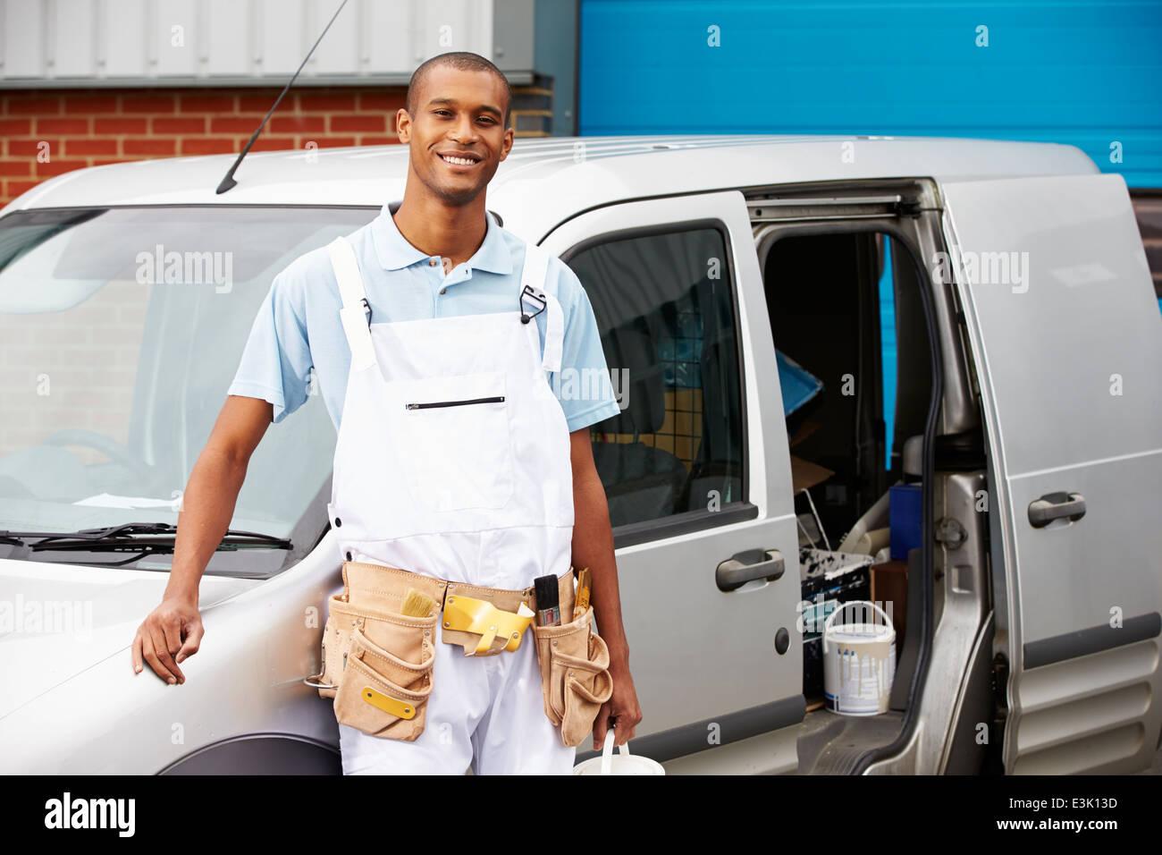Decorator Wearing Overalls Standing Next To Van - Stock Image