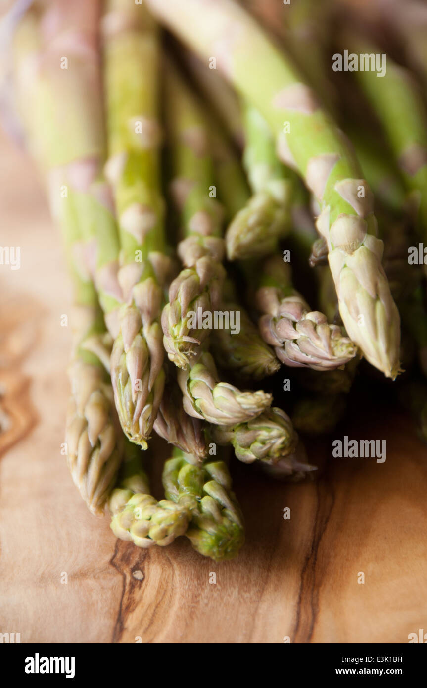 Fresh organic asparagus bunched together on a wooden chopping board - Stock Image