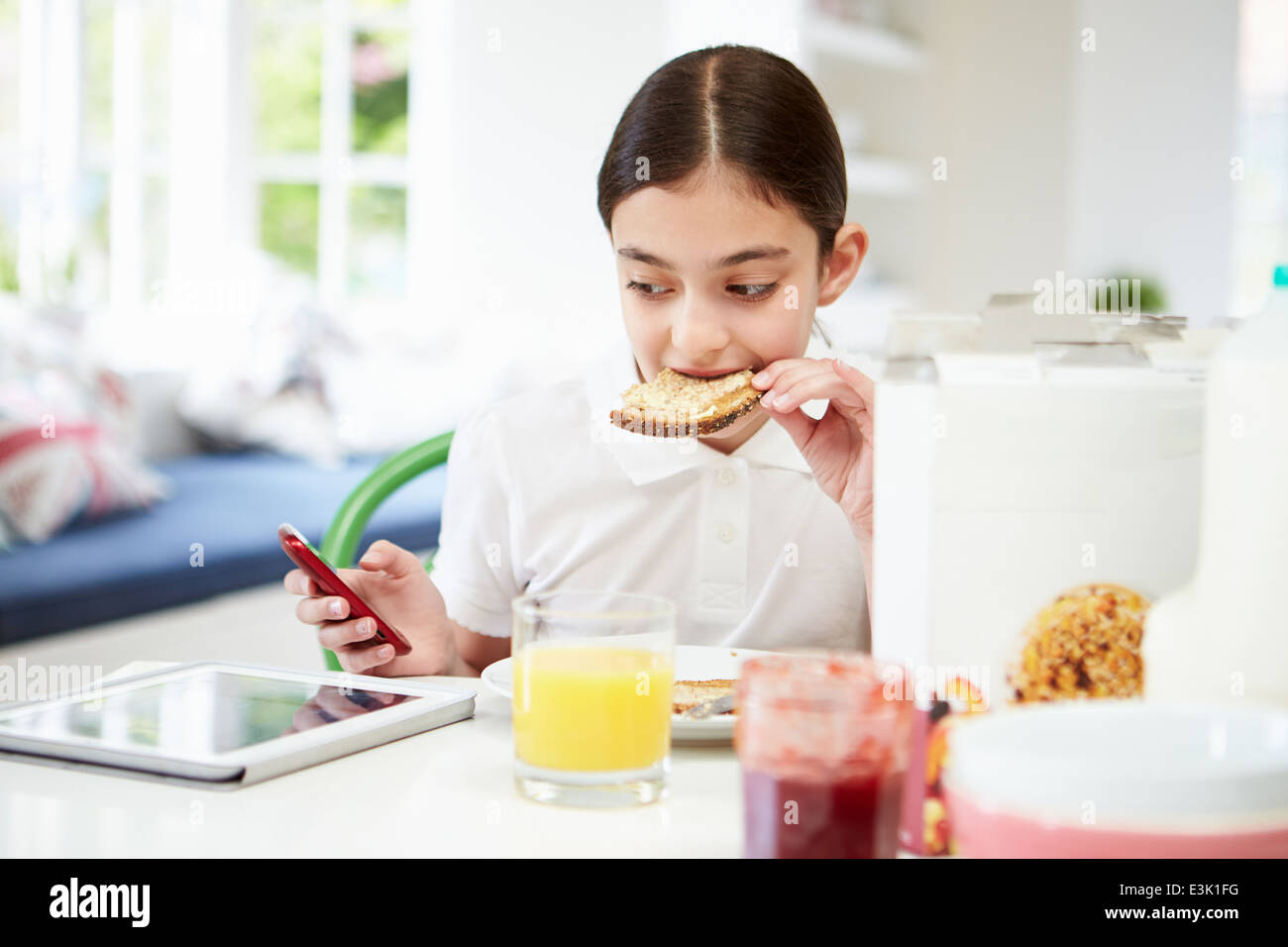 Schoolgirl With Digital Tablet And Mobile Eating Toast - Stock Image