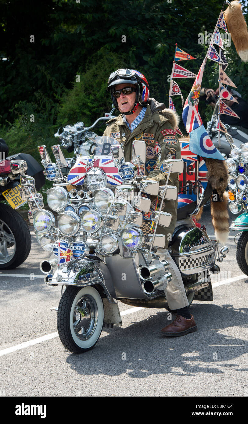 Old Mod riding on his vespa custom scooter with mirrors, lights, logos and union jack decal - Stock Image