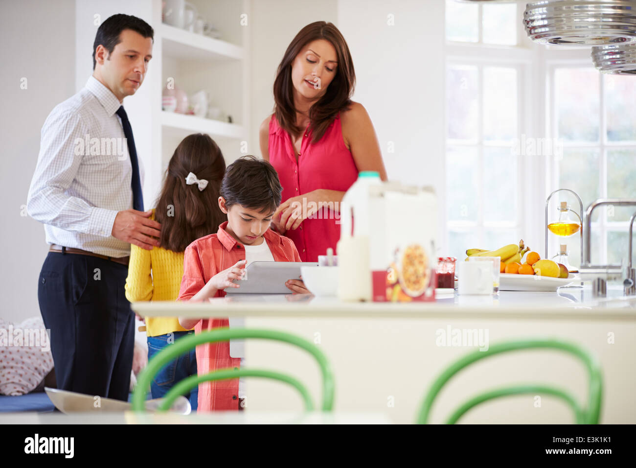Family Helping To Clear Up After Breakfast - Stock Image