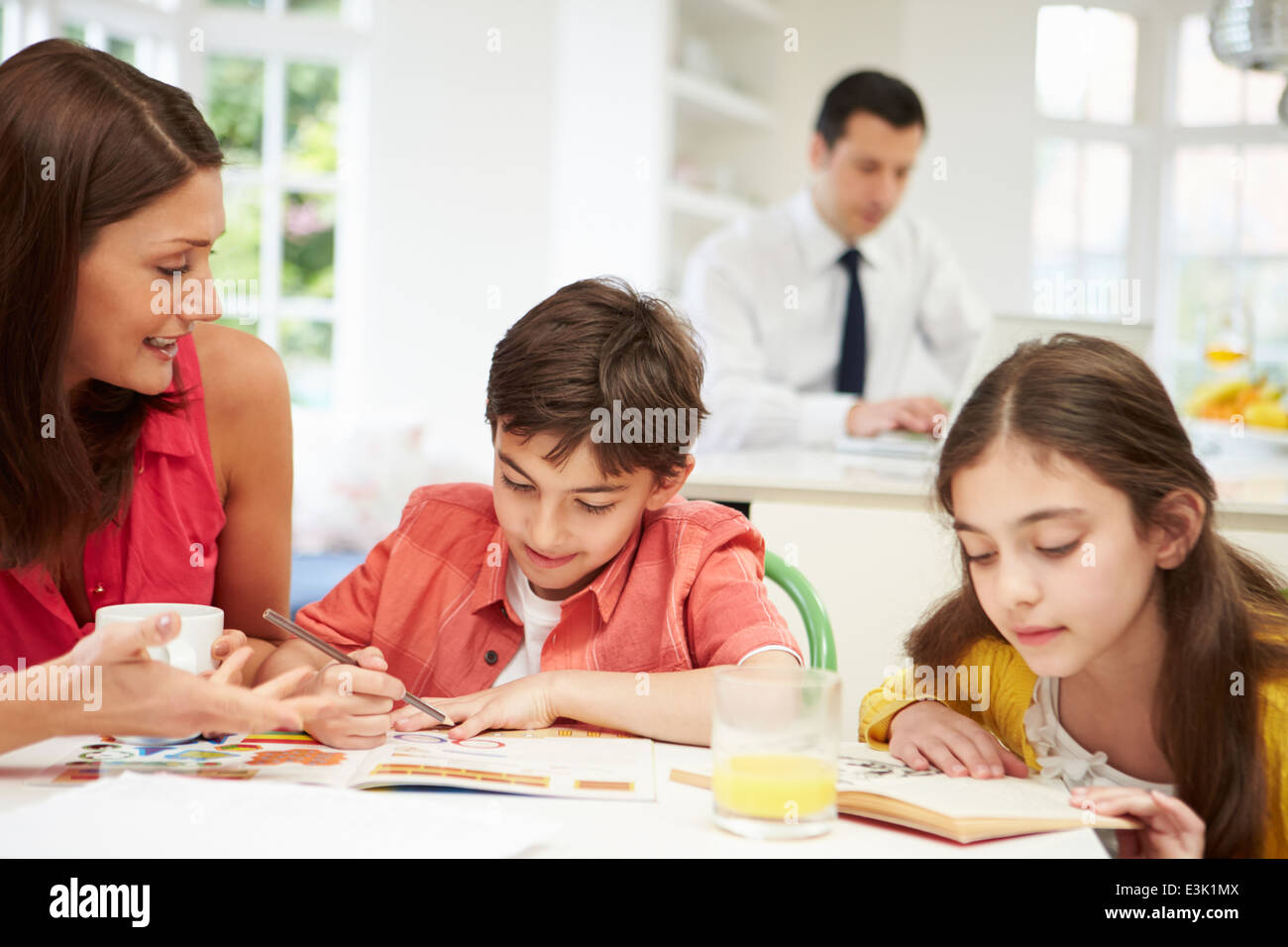 Mum Helps Children With Homework As Dad Works In Background - Stock Image