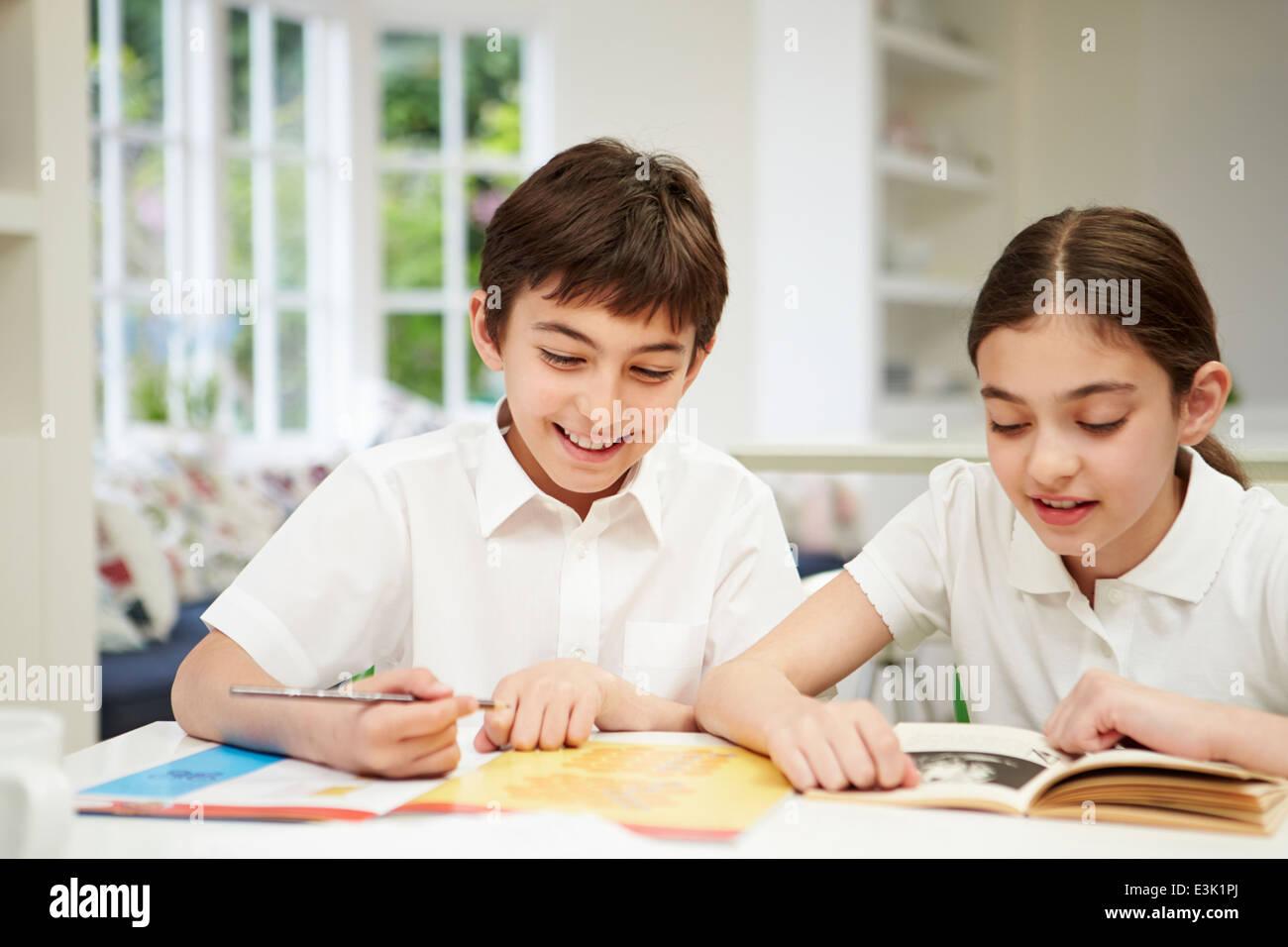 Children Wearing School Uniform Doing Homework In Kitchen Stock ...