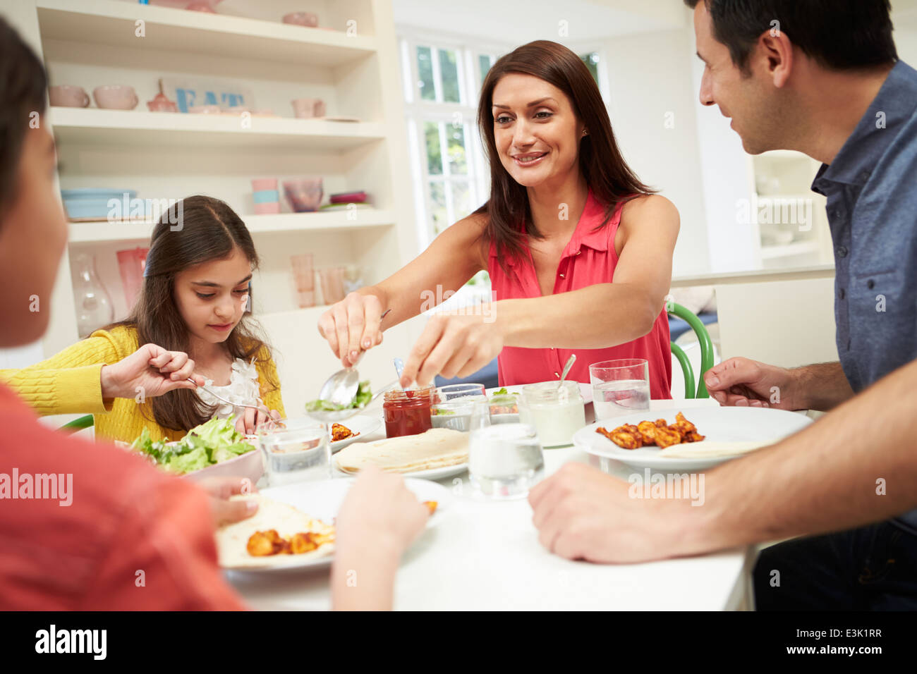 Hispanic Family Sitting At Table Eating Meal Together - Stock Image