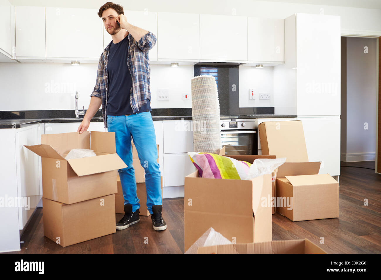 Man Moving Into New Home Talking On Mobile Phone - Stock Image