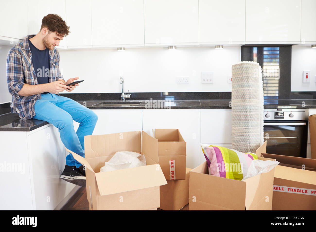 Man Sending Text Message Having Moved Into New Home - Stock Image