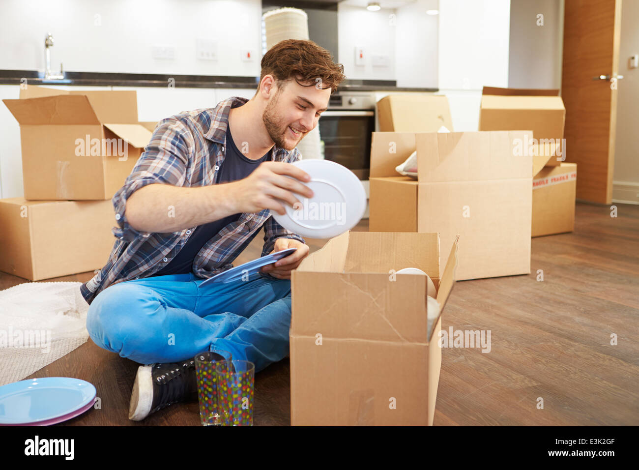 Man Moving Into New Home And Unpacking Boxes - Stock Image