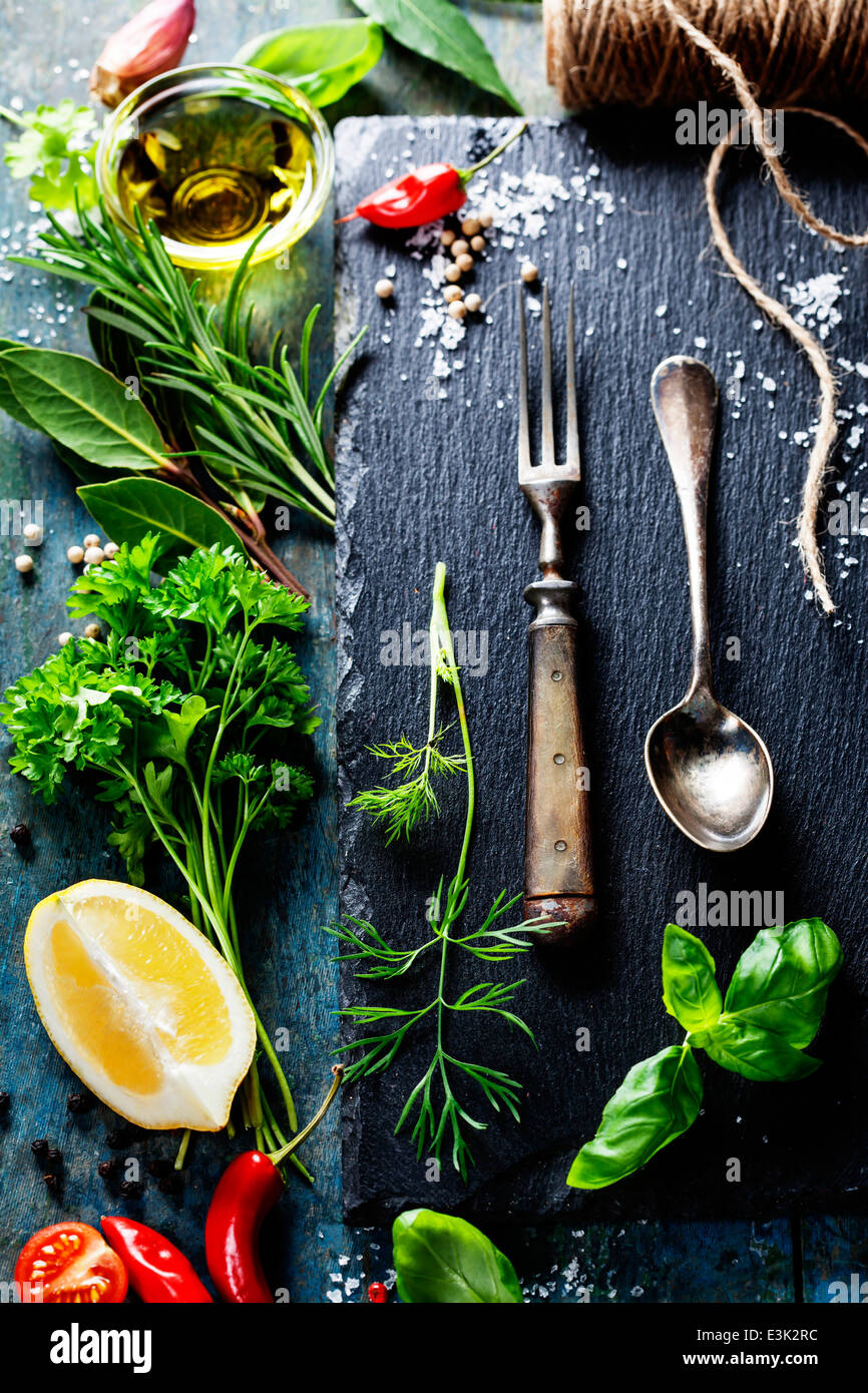 Food background, with herbs, spices, olive oil, salt, lemons and vegetables. Slate and wood background. - Stock Image
