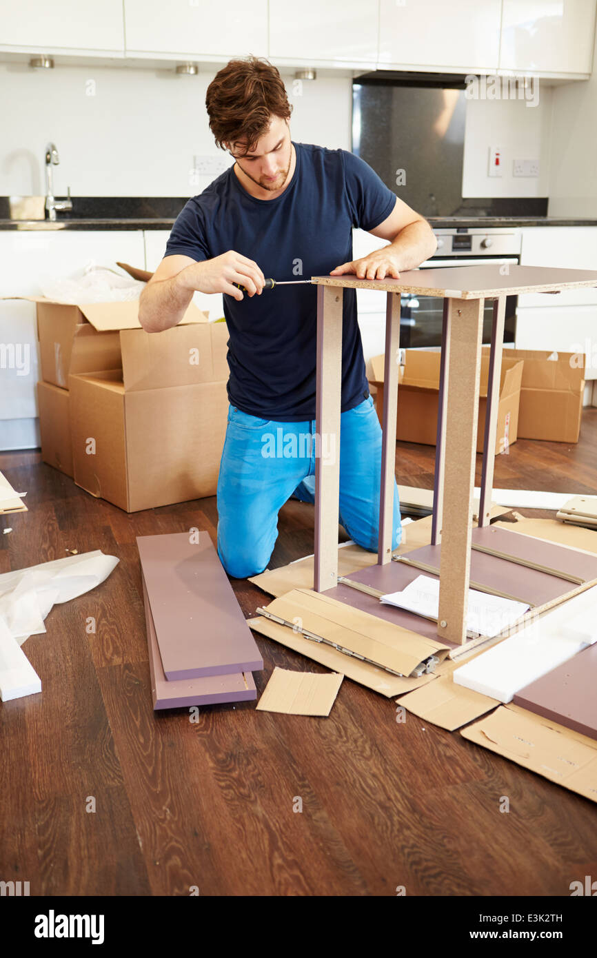 Man Putting Together Self Assembly Furniture In New Home Stock Photo
