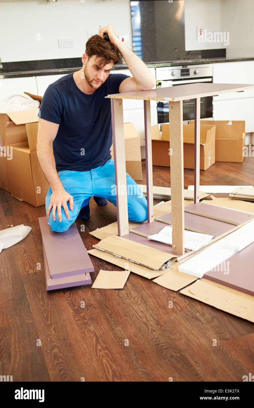 Frustrated Man Putting Together Self Assembly Furniture - Stock Image