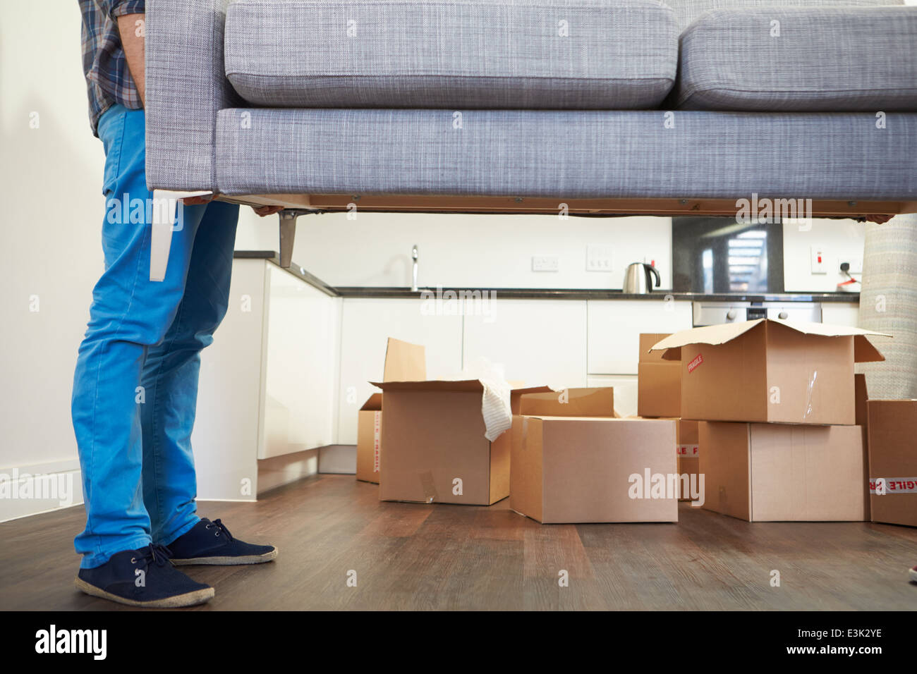 Close Up Of Man Carrying Sofa As He Moves Into New Home - Stock Image
