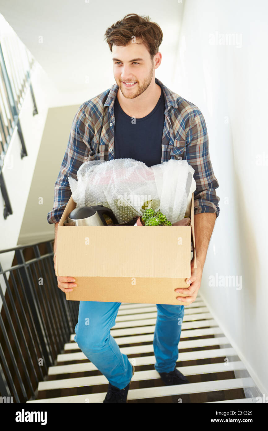 Man Moving Into New Home Carrying Box Upstairs - Stock Image
