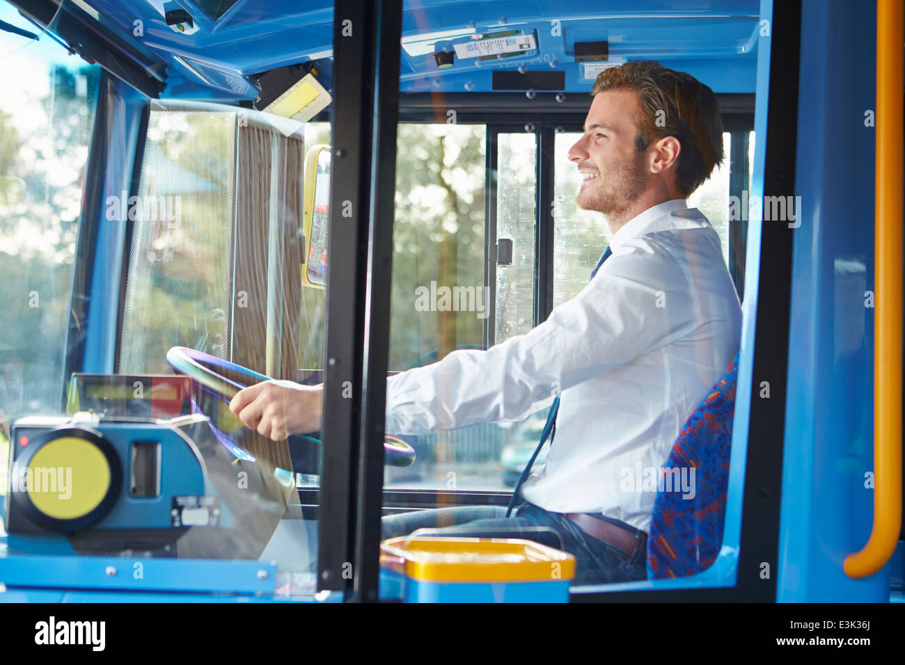 Portrait Of Bus Driver Behind Wheel - Stock Image