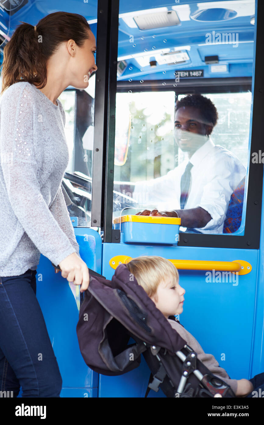 Mother With Child In Pushchair Boarding Bus - Stock Image