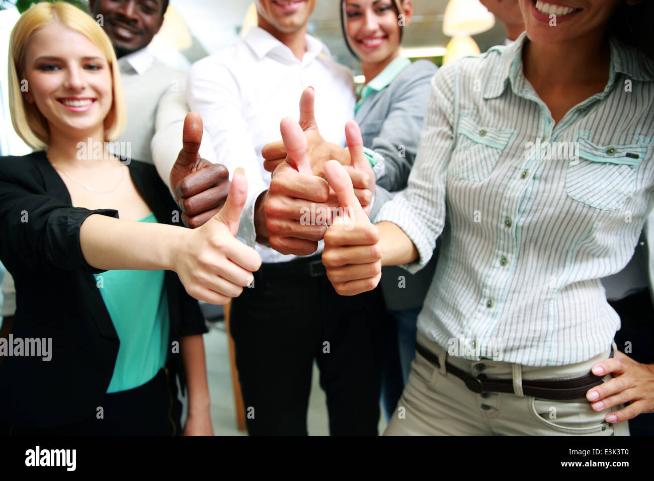 cheerful business group giving thumbs up - Stock Image