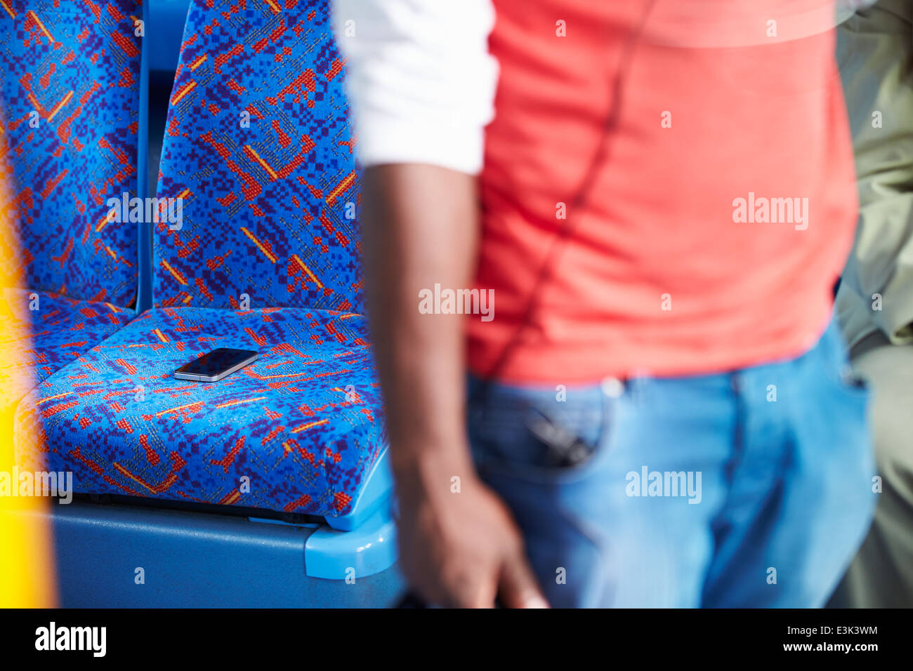 Passenger Leaving Mobile Phone On Seat Of Bus - Stock Image