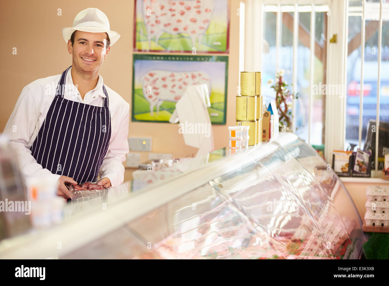 Butcher At Work In Shop - Stock Image