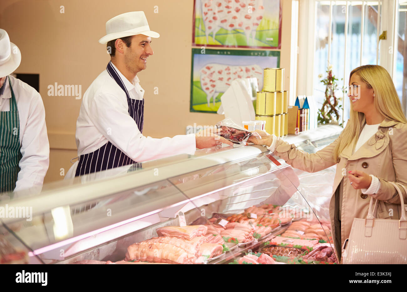 Butcher Serving Customer In Shop - Stock Image