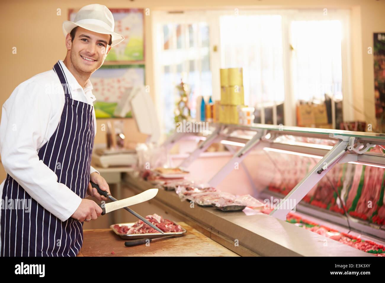 Butcher Preparing Meat In Shop - Stock Image