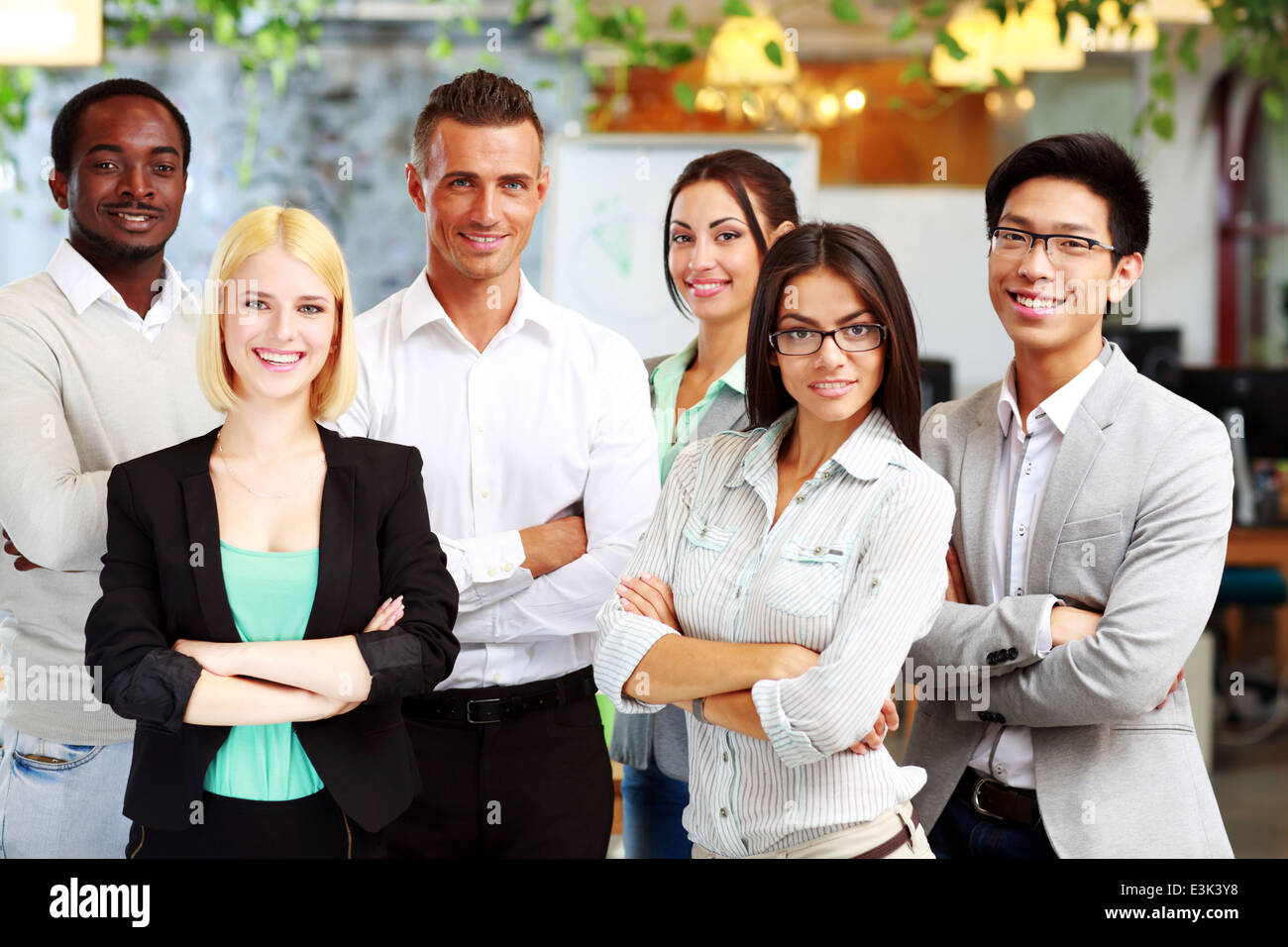 happy group of co-workers standing in office - Stock Image