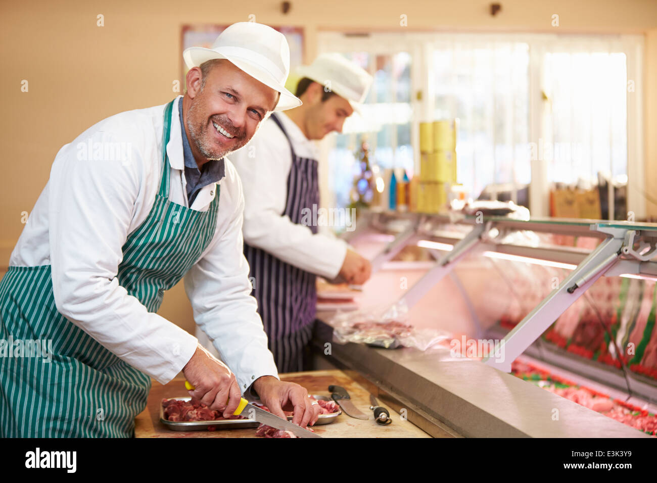 Two Butchers Preparing Meat In Shop - Stock Image
