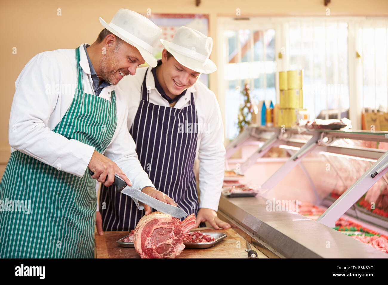 Butcher Teaching Apprentice How To Prepare Meat Stock Photo