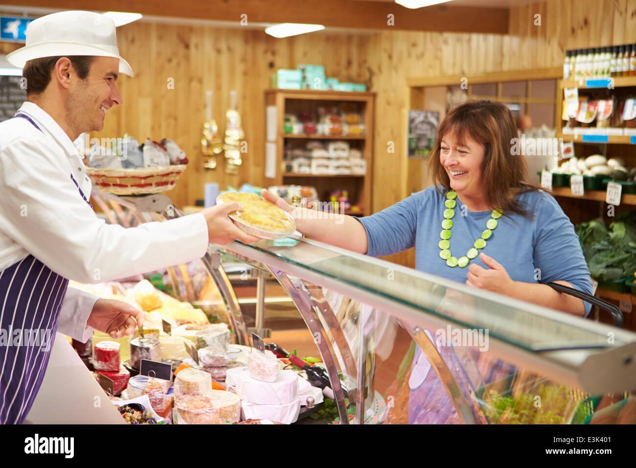 Male Sales Assistant Serving Customer In Delicatessen Stock Photo