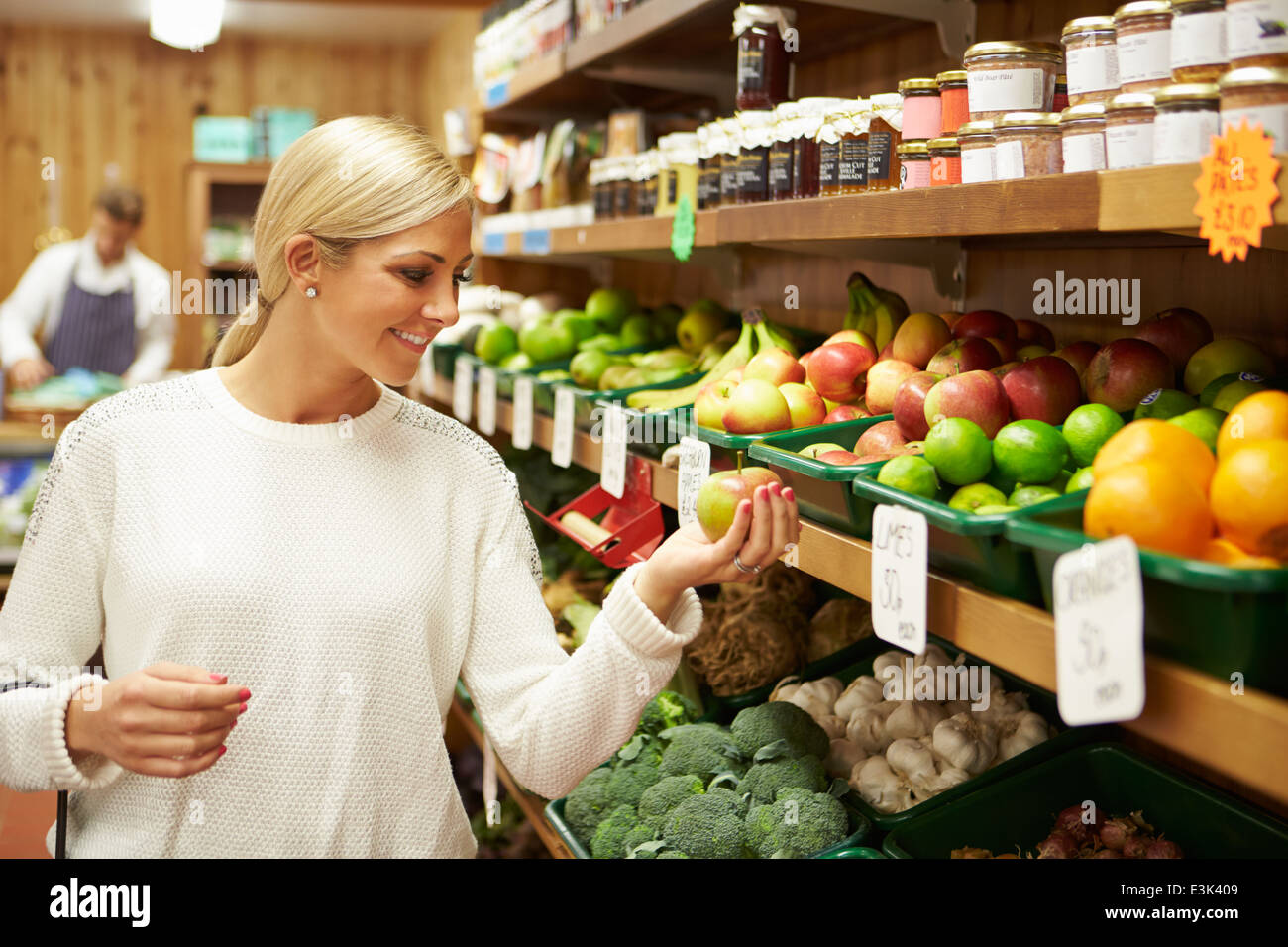Female Customer At Vegetable Counter Of Farm Shop - Stock Image