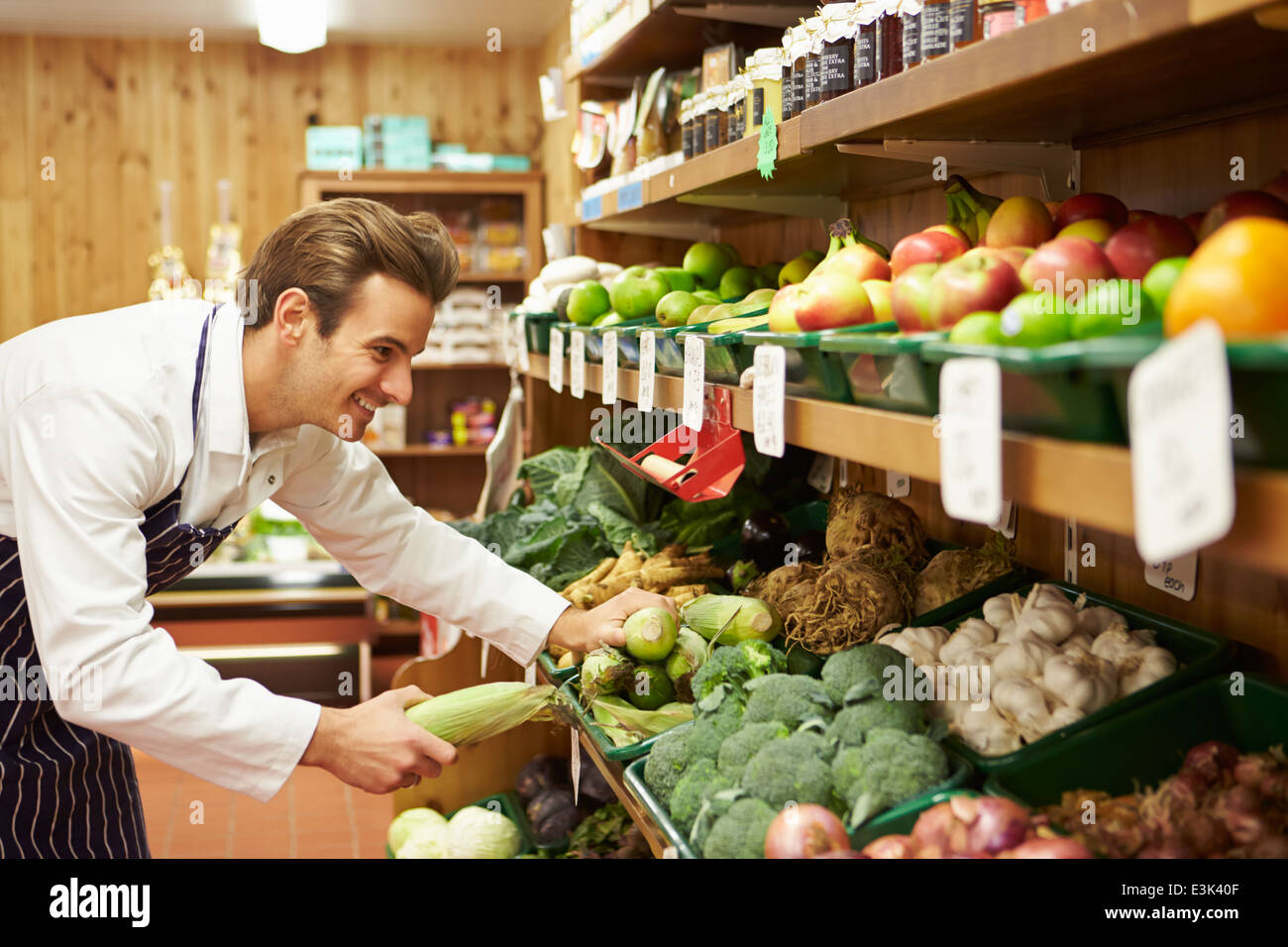 Male Sales Assistant At Vegetable Counter Of Farm Shop - Stock Image