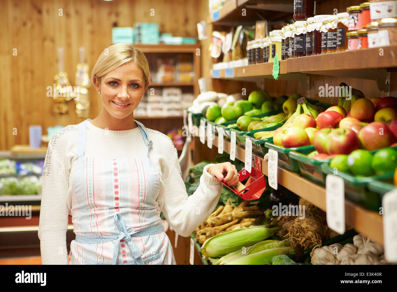 Female Sales Assistant At Vegetable Counter Of Farm Shop - Stock Image