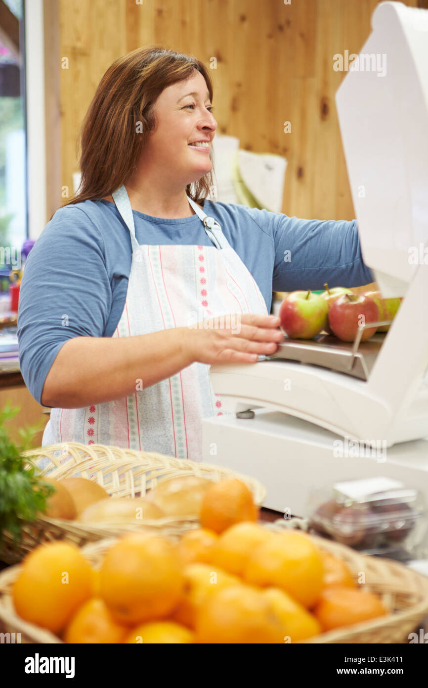 Female Sales Assistant At Checkout Of Farm Shop - Stock Image