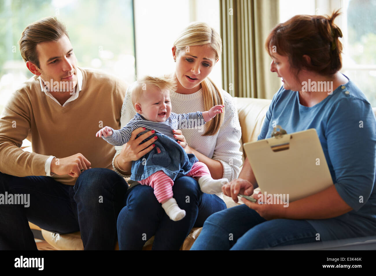 Social Worker Visiting Family With Young Baby - Stock Image