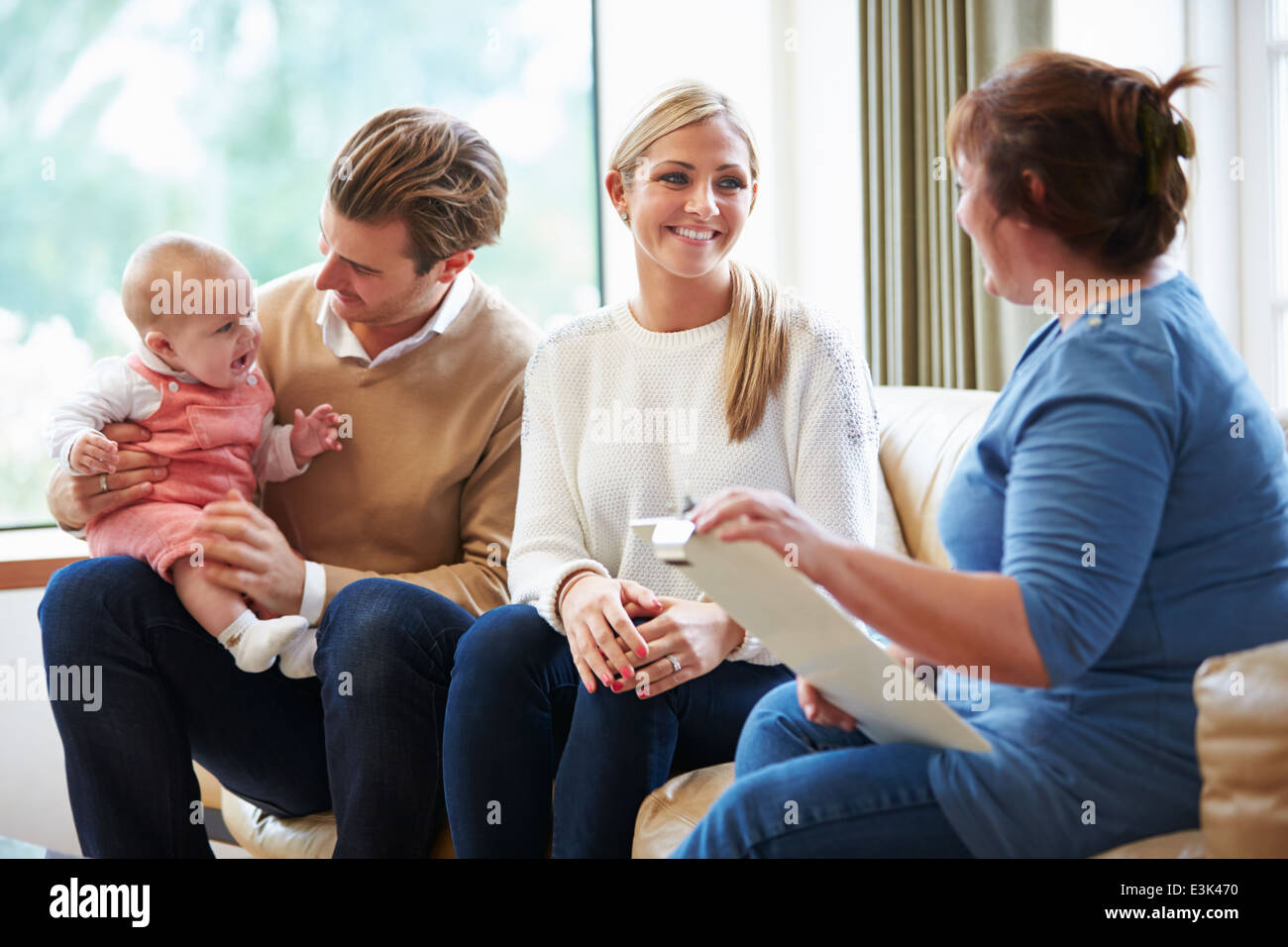 Health Visitor Talking To Family With Young Baby - Stock Image