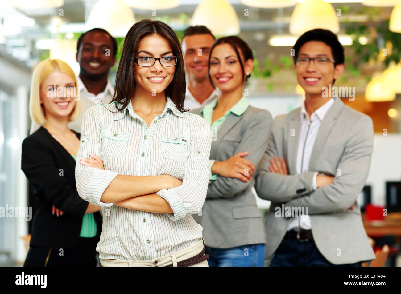 Smiling group of co-workers standing in office - Stock Image