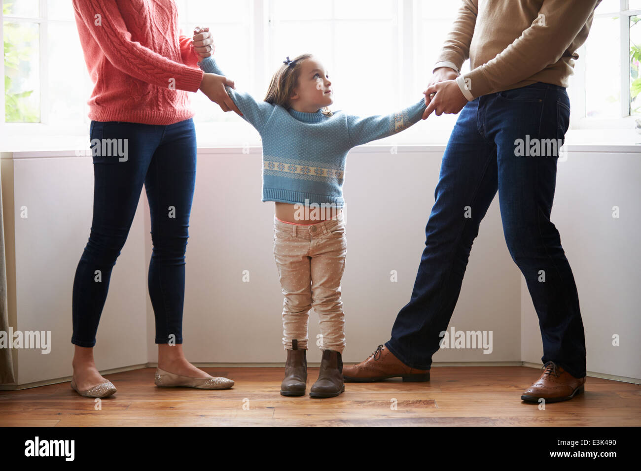 Two Parents Fighting Over Child In Divorce Concept - Stock Image