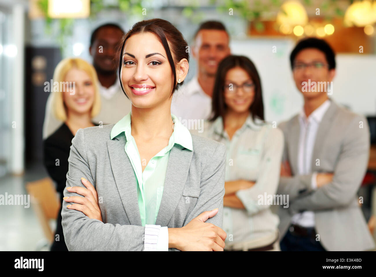 Cheerful group of co-workers standing in office - Stock Image