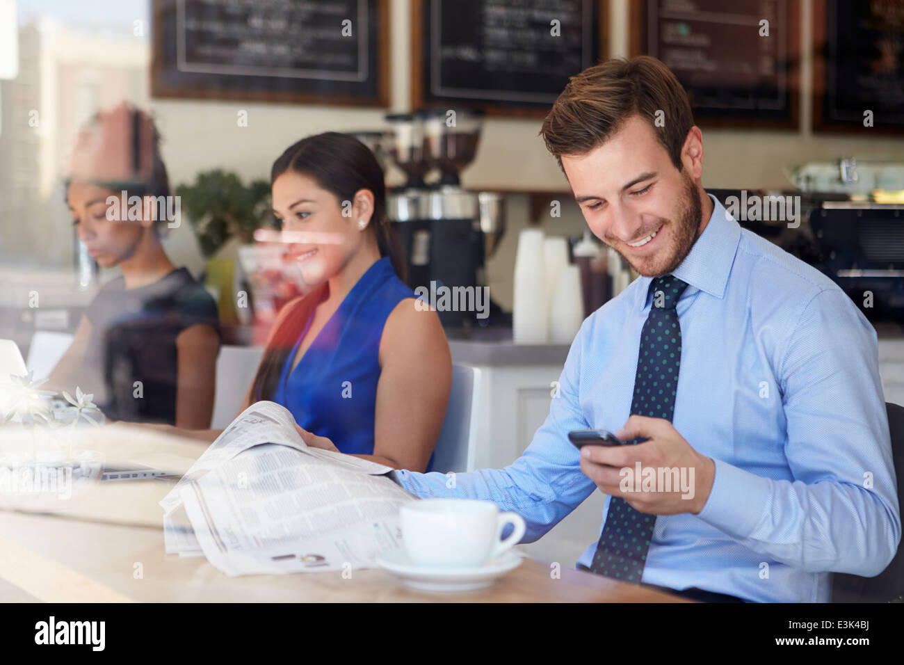 Businessman With Mobile Phone And Newspaper In Coffee Shop - Stock Image