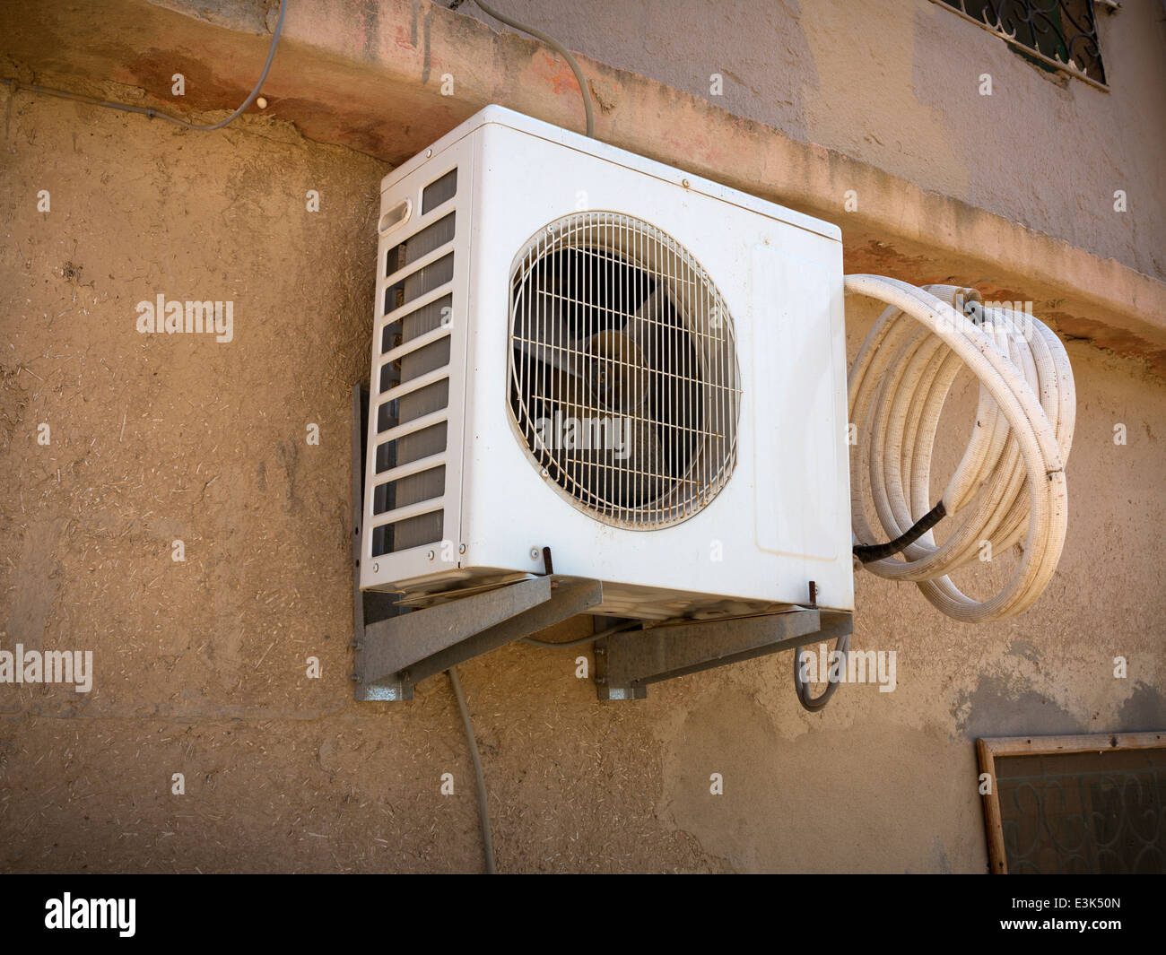 An externally wall mounted air conditioning unit with a coil of plastic hosing mounted on a dusty mud-brick wall - Stock Image