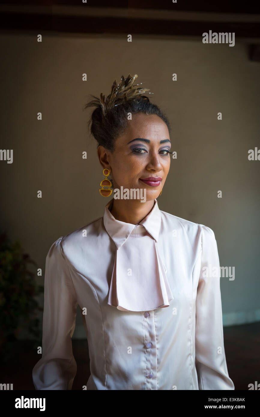 mysterious oriental woman portrait wearing earrings and feathers - Stock Image
