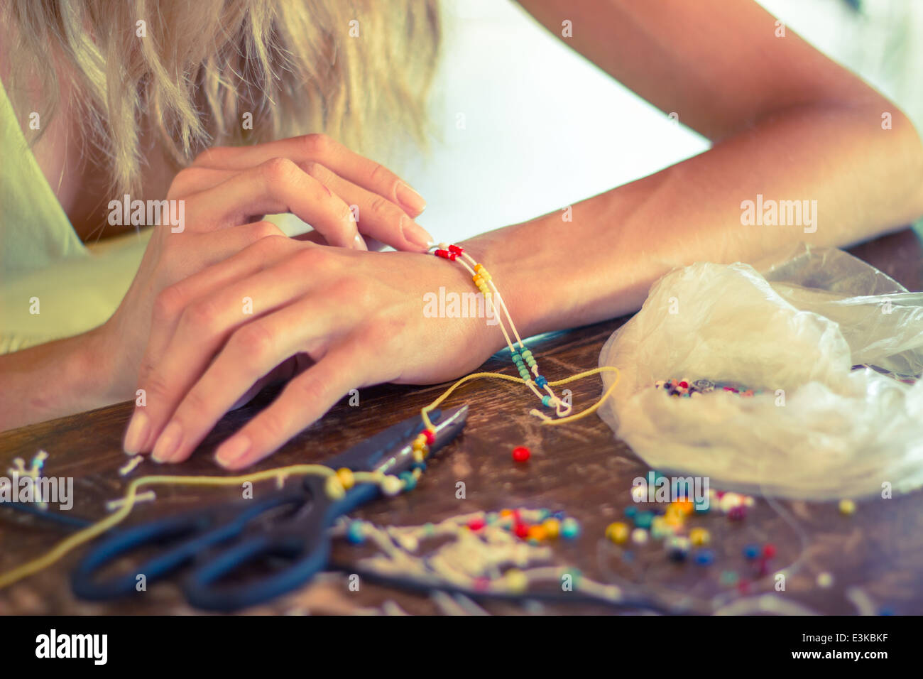 woman hands making craft crafting hobby bracelet colorful beads rope - Stock Image