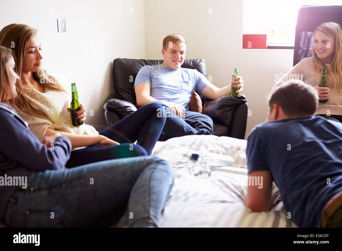 Group Of Teenagers Drinking Alcohol In Bedroom - Stock Image