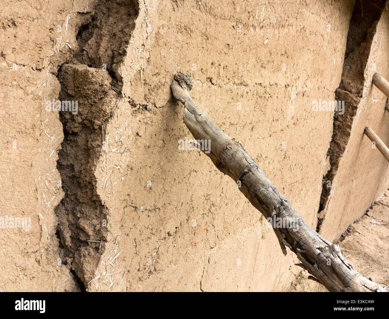 A cracked and leaning section of mud-brick wall being supported by a wooden prop - Stock Image