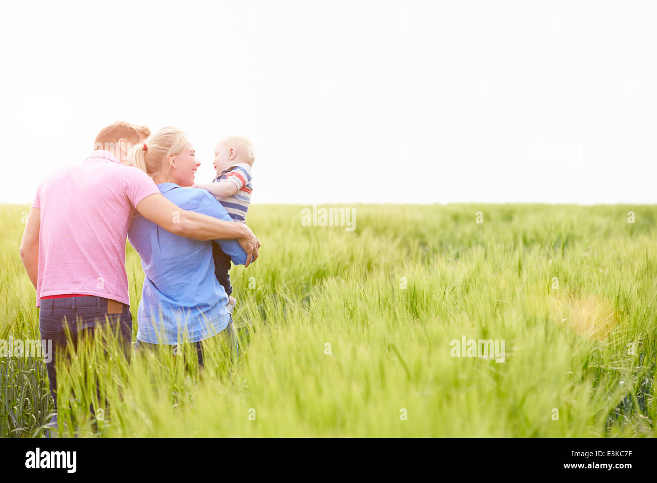 Family Walking In Field Carrying Young Baby Son - Stock Image
